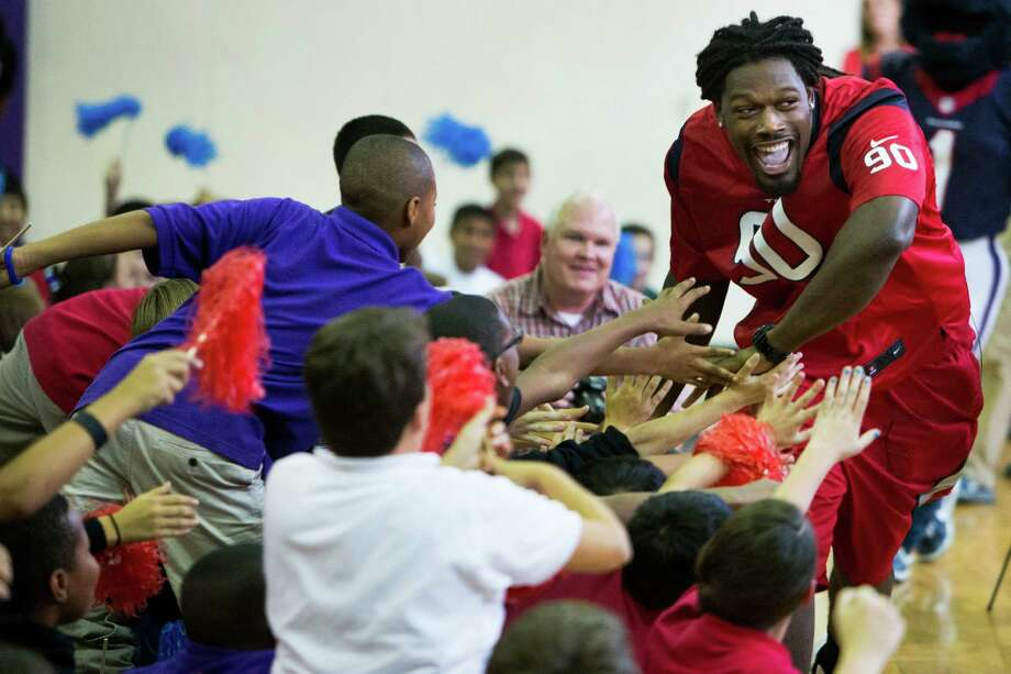 The Texans' Jadeveon Clowney makes an enthus-iastic entrance Tuesday at Lanier Middle School. Photo: Brett Coomer, Staff / © 2014  Houston Chronicle
