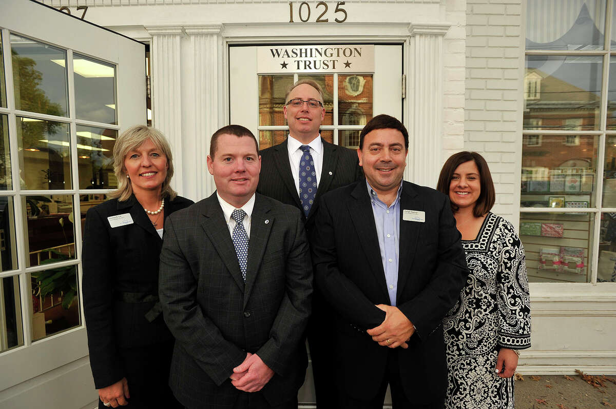 Washington Trust Mortgage Company employees from left: Darlene Lee, senior mortgage loan officer; Kevin Kinahan, mortage loan officer; James Gueltzow, executive vice president; George Zygmont, senior mortgage loan officer; Jaclyn Pioli, loan processor, pose for a photograph in front of Washington Trust's new location along Boston Post Road in Darien, Conn., on Tuesday, Sept. 30, 2014.