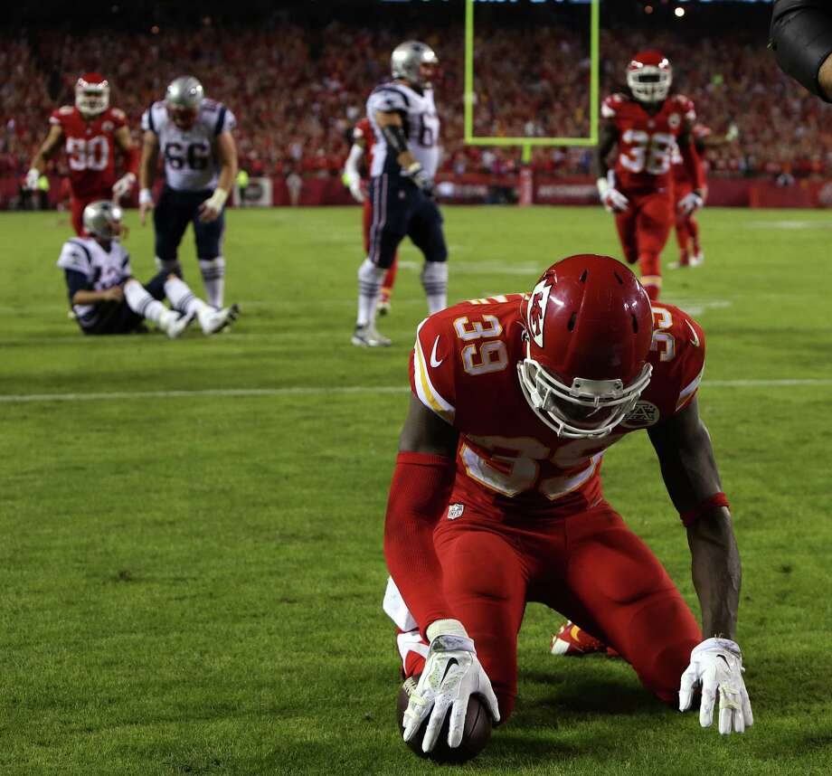 In this photo taken on Monday, Sept. 29, 2014, Kansas City Chiefs free safety Husain Abdullah (39) bows his head in prayer after intercepting a pass from New England Patriots quarterback Tom Brady (12), seated on field at left, and returning it for a touchdown during the fourth quarter of an NFL football game in Kansas City, Mo.  Abdullah was penalized on the play. The NFL said Tuesday, Sept. 30, 2104, that Abdullah should not have been penalized for unsportsmanlike conduct when he dropped to his knees in prayer after an interception. (AP Photo/The Boston Globe, Barry Chin)  BOSTON HERALD OUT, QUINCY OUT; NO SALES ORG XMIT: MABOD301 Photo: Barry Chin / The Boston Globe