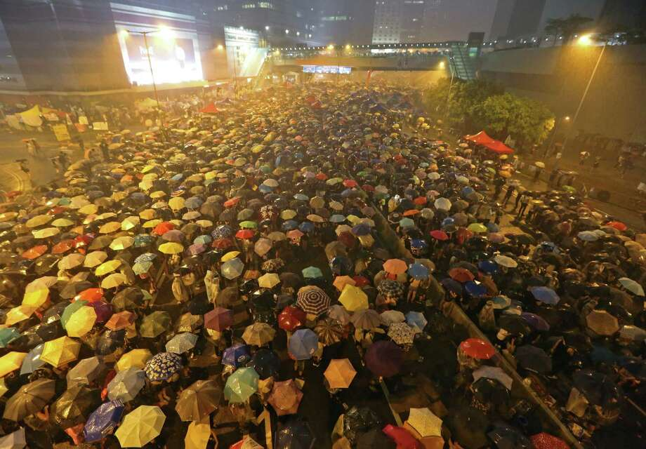 Pro-democracy protesters hold umbrellas under heavy rain in a main street near the government headquarters in Hong Kong late Tuesday, Sept. 30, 2014. The protesters demanded that Hong Kong's top leader meet with them on Tuesday and threatened wider actions if he did not, after he said China would not budge in its decision to limit voting reforms in the Asian financial hub. (AP Photo) ORG XMIT: HK101 / AP