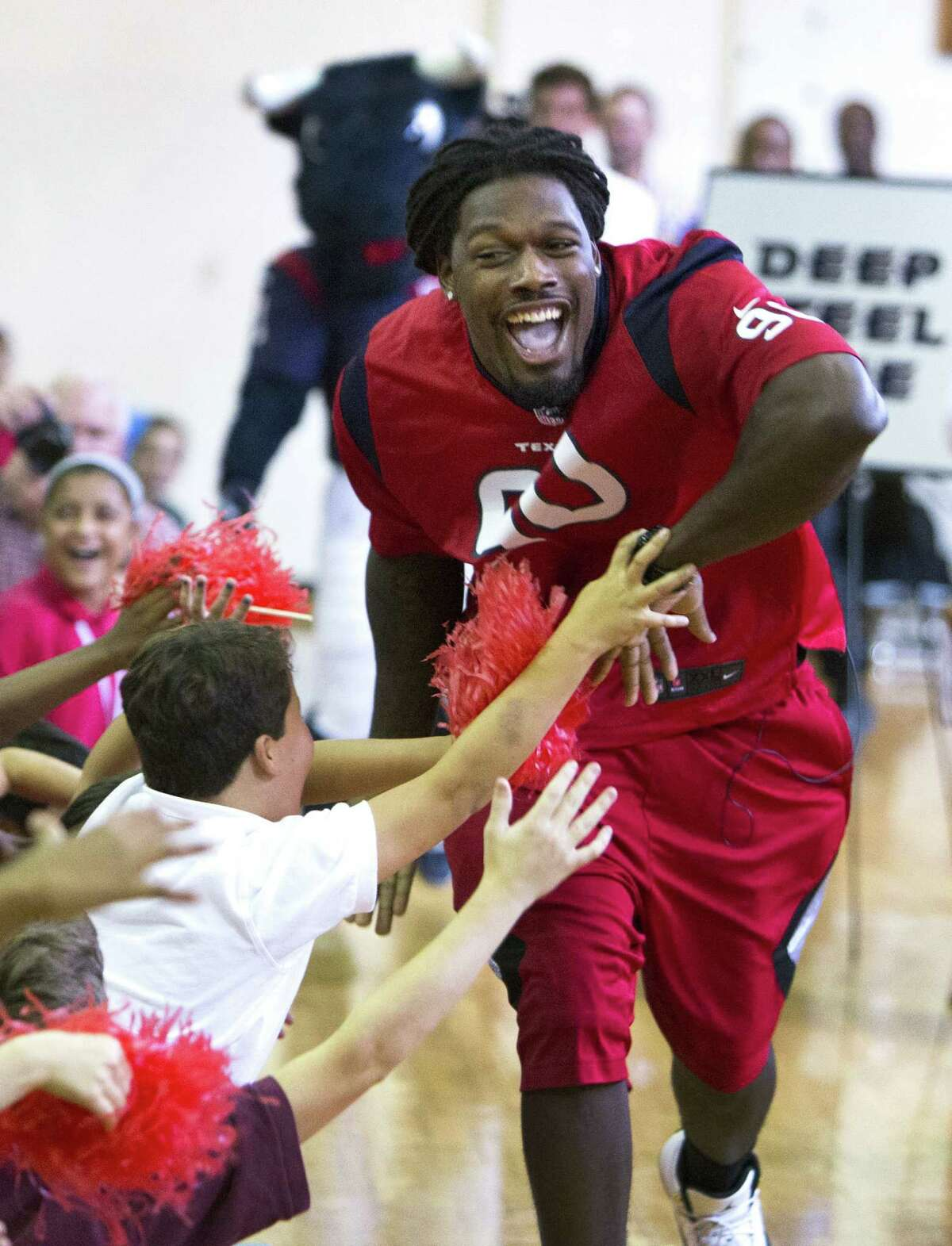 Texans linebacker Jadeveon Clowney slaps hands with students at Lanier Middle School in Houston on Tuesday.