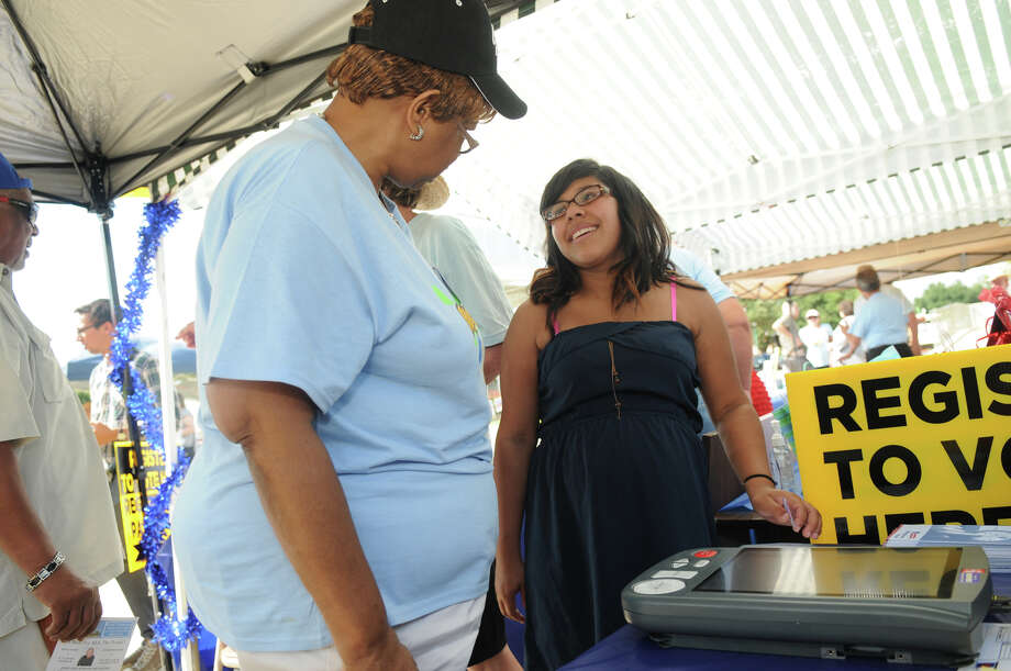 Shelba Richardson, left, an official of the Montgomery County Democratic Party, introduces Brenda Carrillo, 18, a 2014 graduate of Caney Creek High School, to the e-slate voting machine during a Conroe event. Photo: Jerry Baker, Freelance