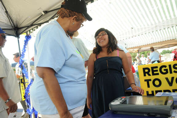 Shelba Richardson, left, an official of the Montgomery County Democratic Party, introduces Brenda Carrillo, 18, a 2014 graduate of Caney Creek High School, to the e-slate voting machine during a Conroe event.