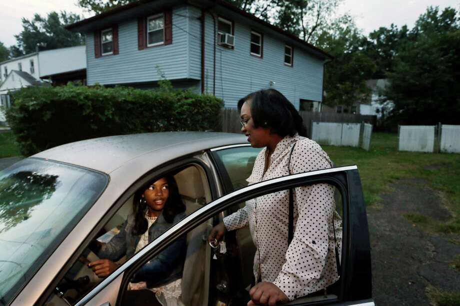 Tysha Wheeler-Timmons, right, talks to daughter Shayla as they leave home before sunrise Tuesday, Sept. 30, 2014, in Rahway, N.J. Wheeler-Timmons found a tutor through the site WyzAnt for her daughter, Shayla, a rising high school senior. And she took a part-time security job to fund the tutoring and her daughter's academic opportunities. (AP Photo/Mel Evans) ORG XMIT: NYBZ217 Photo: Mel Evans / AP