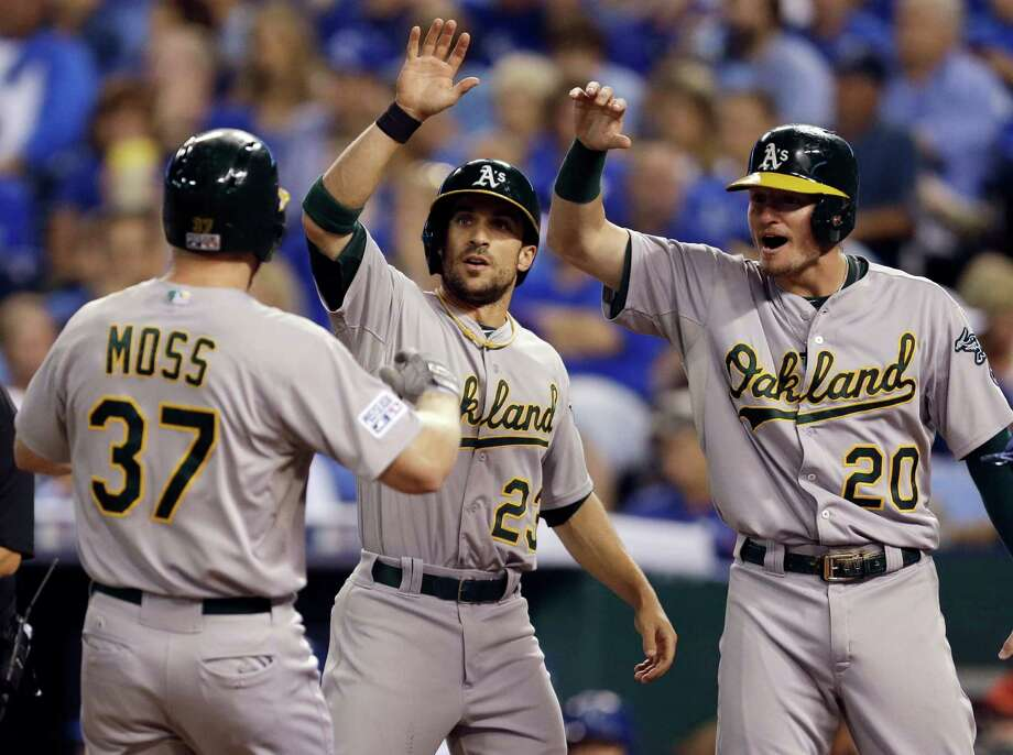 Oakland Athletics' Brandon Moss, left, is congratulated by teammates Sam Fuld and Josh Donaldson, right, as he arrives at home after hitting a three-run home run during the sixth inning of the AL wild-card playoff baseball game against the Kansas City Royals on Tuesday, Sept. 30, 2014, in Kansas City, Mo. (AP Photo/Jeff Roberson) ORG XMIT: MOJR123 Photo: Jeff Roberson / AP
