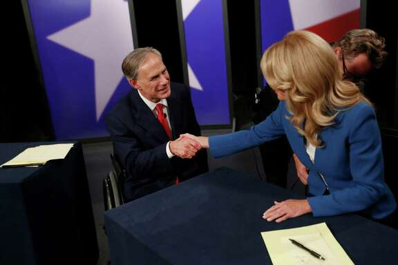 Texas State Senator Wendy Davis, right, Democratic Gubernatorial candidate, and Texas Attorney General Greg Abbott, left, Republican Gubernatorial candidate, shake hands before the final gubernatorial debate in a KERA-TV studio in Dallas on Tuesday Sept. 30, 2014. Ebola, ethics and education were among the issues that dominated the final debate between the two. (AP Photo/The Dallas Morning News, Andy Jacobsohn, Pool)