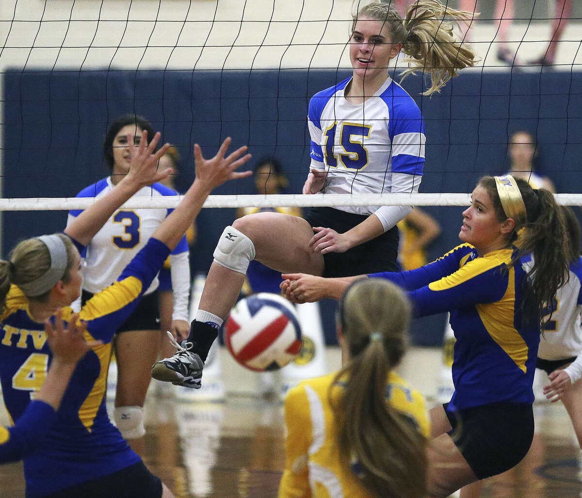 Alamo Heights' McKay Kyle (15) enjoys the scramble she created on the other side of the net with her spike during the Mules' three-set victory over District 27-5A rival Kerrville Tivy.