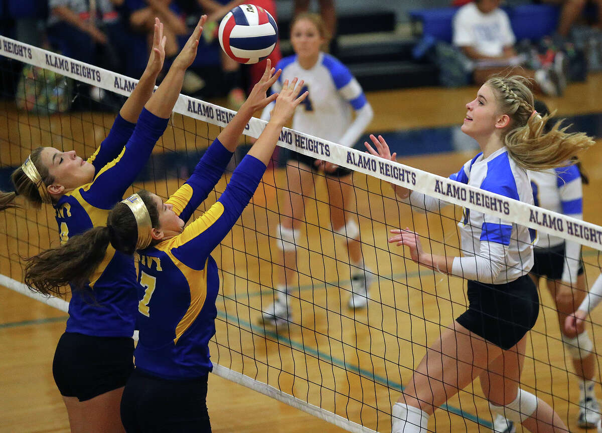 Lady Mule McKay Kyle (right) sinks the ball over the Antler defense as Alamo Heights hosts Tivy at the Alamo Heights Gym on September 30, 2014.