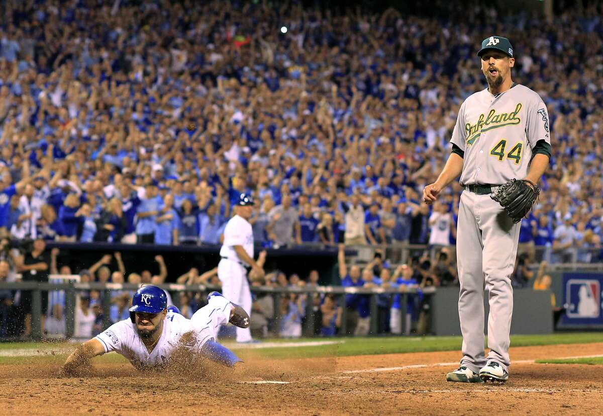 Kansas City Royals' Eric Hosmer, left, scores on a wild pitch by Oakland Athletics relief pitcher Luke Gregerson, right, during the eighth inning of the AL wild-card playoff baseball game Tuesday, Sept. 30, 2014, in Kansas City, Mo. (AP Photo/Jeff Roberson)