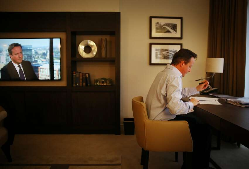 BIRMINGHAM, ENGLAND - SEPTEMBER 30: Prime Minister David Cameron prepares his keynote speech in his hotel room at the Conservative party conference as his image appears on a TV news broadcast (L) on September 30, 2014 in Birmingham, England. Tomorrow is the final day of conference. (Photo by Peter Macdiarmid/Getty Images) *** BESTPIX ***