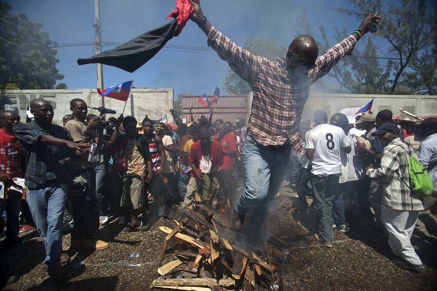 A supporter of former Haitian President Jean-Bertrand Aristide walks over burning wood as part of a voodoo ceremony before the start of a protest on the anniversary of the 1991 military coup that ousted Aristide, the country's first democratically elected leader, in Port-au-Prince, Haiti, Tuesday, Sept. 30, 2014. The march Tuesday marked the date that the military ousted Aristide less than a year into his first term as president. It also comes amid fears he will be arrested for failing to heed a court summons to testify in a corruption case. (AP Photo/Dieu Nalio Chery)