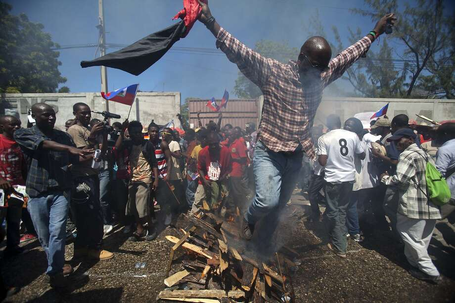 A supporter of former Haitian President Jean-Bertrand Aristide walks over burning wood as part of a voodoo ceremony before the start of a protest on the anniversary of the 1991 military coup that ousted Aristide, the country's first democratically elected leader, in Port-au-Prince, Haiti, Tuesday, Sept. 30, 2014. The march Tuesday marked the date that the military ousted Aristide less than a year into his first term as president. It also comes amid fears he will be arrested for failing to heed a court summons to testify in a corruption case. (AP Photo/Dieu Nalio Chery) Photo: Dieu Nalio Chery, Associated Press