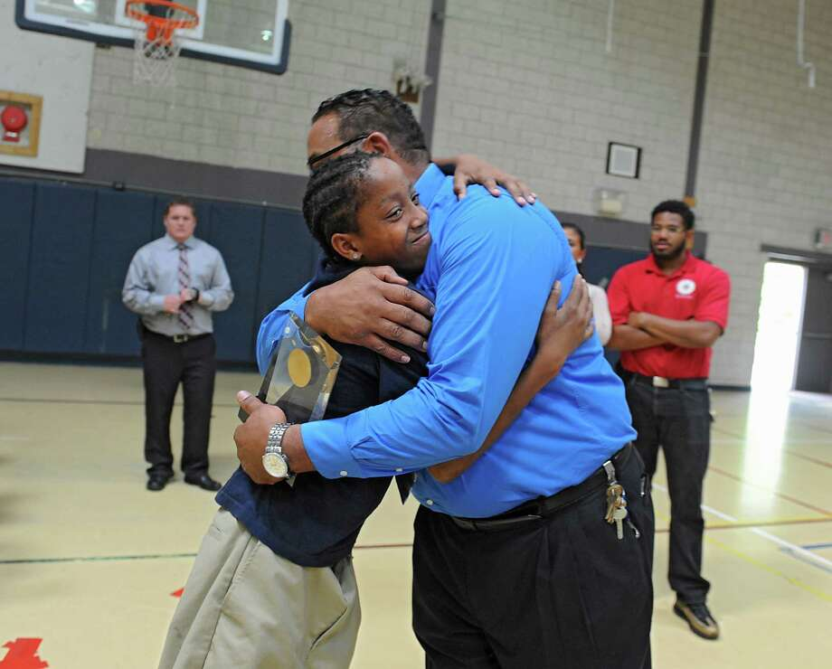 Troy Kennedy gets a hug from student Raequan Tarver, 13, of Albany after receiving the Distinguished LaSallean Educator Award at LaSalle School on Tuesday, Sept. 30, 2014 in Albany, N.Y.  Kennedy started there as a troubled teen himself and is now being honored nationally as an outstanding teacher. Kennedy's son Deandre Kennedy, who is a child care worker at the school, stands at right. (Lori Van Buren / Times Union) Photo: Lori Van Buren / 10028831A
