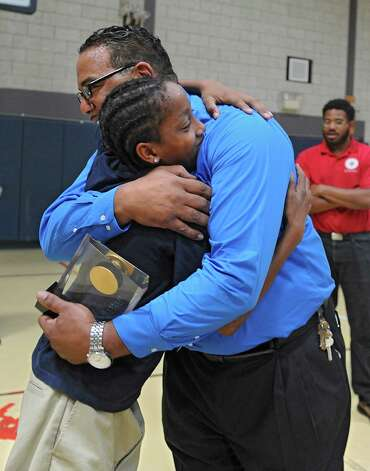 Troy Kennedy gets a hug from student Raequan Tarver, 13, of Albany after receiving the Distinguished LaSallean Educator Award at LaSalle School on Tuesday, Sept. 30, 2014 in Loudonville, N.Y.  Kennedy started there as a troubled teen himself and is now being honored nationally as an outstanding teacher. Kennedy's son Deandre Kennedy who is a child care worker at the school stands at right. (Lori Van Buren / Times Union) Photo: Lori Van Buren / 10028831A