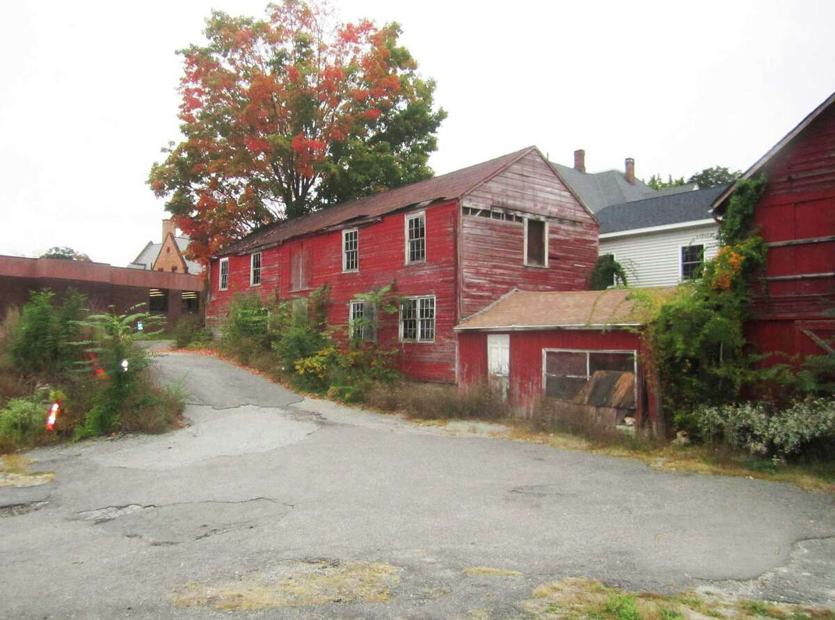 Town-owned property in the New Milford village center, including two old barns off Church Street, is now targeted for outdoor art use. The property, located between Main Street and East Street, adjoins the east side of the New Milford Public Library property, left. October 2014.