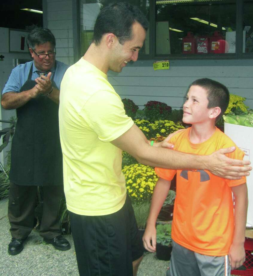 """Matthew Hernandez, 11,, of Sherman bonds with Joe Moravsky during the """"American Ninja Warrior"""" standout's """"Meet and Greet"""" at Sherman IGA. Store owner Mike Luzi, left, applauds the tandem. Sept. 20, 2014 Photo: Norm Cummings / The News-Times"""
