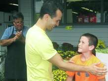 "Matthew Hernandez, 11,, of Sherman bonds with Joe Moravsky during the ""American Ninja Warrior"" standout's ""Meet and Greet"" at Sherman IGA. Store owner Mike Luzi, left, applauds the tandem. Sept. 20, 2014"