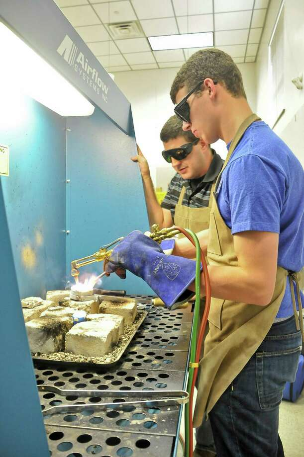 San Jacinto College art metals professor Jeffrey McGee (back) observes student Collin Freeman as he melts bronze to cast a small mold for one of his first projects.