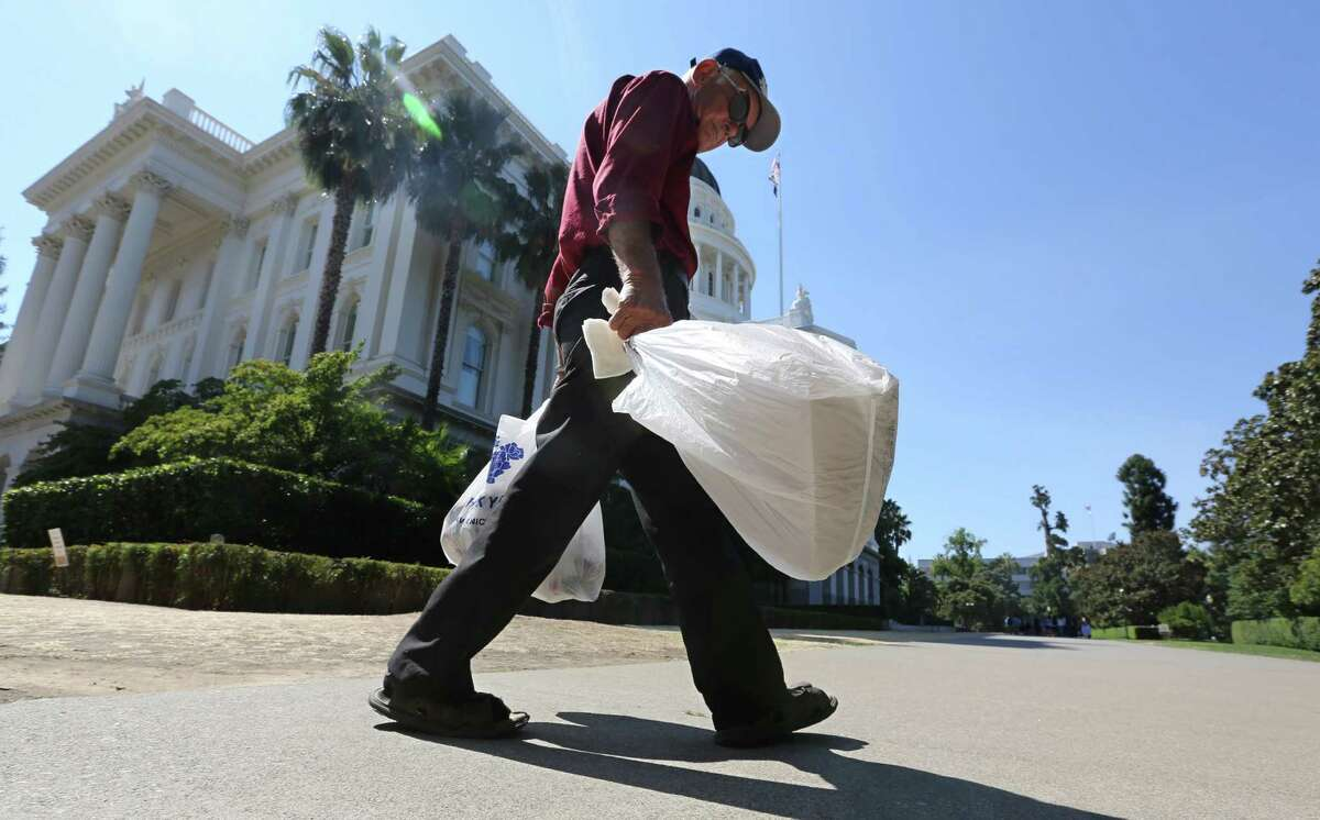 FILE-This file photo taken Tuesday, Aug. 12, 2014, plastic single-use bags are carried past the State Capitol in Sacramento, Calif. Gov. Jerry Brown has signed legislation on Tuesday, Sept. 30, 2014 imposing the nation's first statewide ban on single-use plastic bags. (AP Photo/Rich Pedroncelli,File)