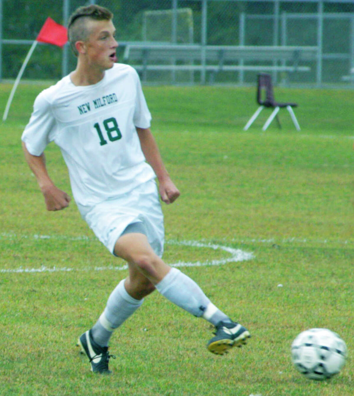 Cooper Knight of the Green Wave delivers a pass during New Milford High School boys' soccer's 2-1 victory over Pomperaug, Sept. 20, 2014 at NMHS.