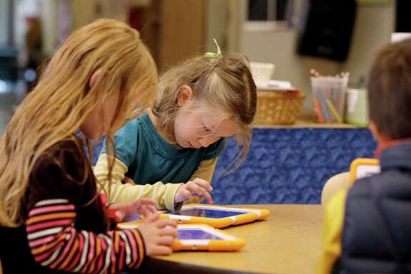 Talia Levitt (left), 7, Charlotte Klingaman, 6, and Aiden Crott, 7, work on their ScratchJr programs.