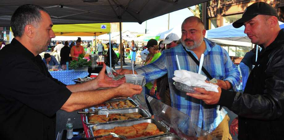Bulgarian chefs Petar Bachvarov (center in blue shirt) and Ivan Manchev (in hat) chat about Eastern European food with Armin Hrelja, whose family owns Euro Delicacies, at the Troy famers market on Saturday, Sept. 27, 2014. (Steve Barnes/Times Union)