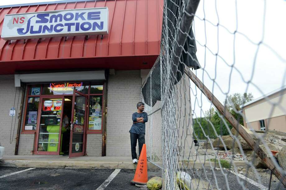 King Muhammad, a 20-year manager at Smoke Junction, which plans to move into the newly constructed plaza next door, looks through the fence at the work going on there Tuesday, Sept. 30, 2014, in Derby, Conn. The plaza at the corner of Pershing and Division streets in Derby was supposed to be knocked down so a new Walgreens could be built, but Walgreens pulled out of the deal. Photo: Autumn Driscoll / Connecticut Post