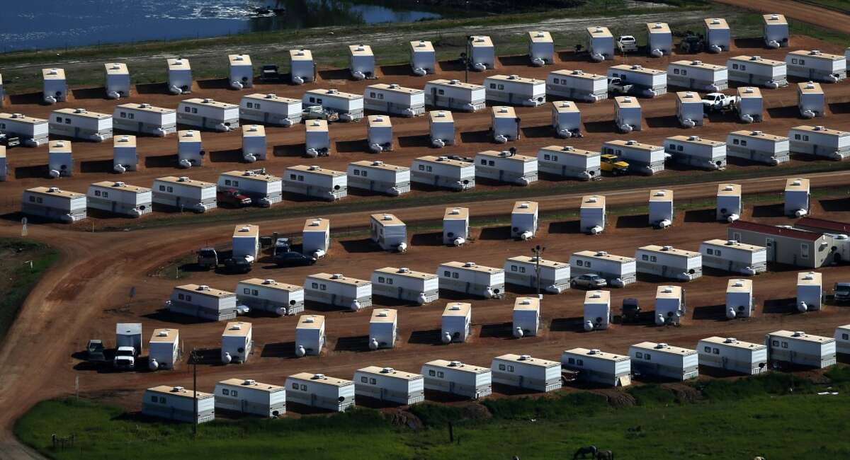 This June 12, 2014, aerial photo shows a temporary housing development in Watford City, N.D. Oil patch towns, outposts of oil production now struggling to become livable cities, are trying to keep up with the oil boom. And housing, from apartment blocks in front of oil wells and flares to sprawling trailer parks on bluffs, are popping up across the countryside. (AP Photo/Charles Rex Arbogast)