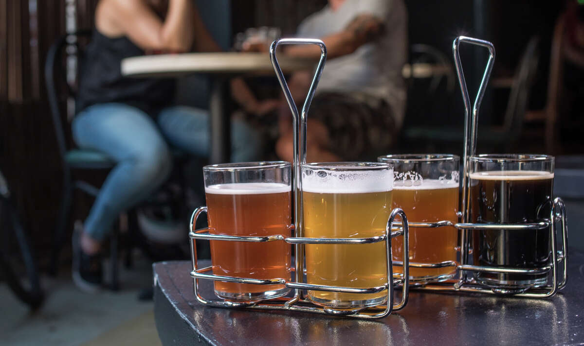 At Woods Bar & Brewery in Oakland, clockwise from top, try a taste sampler for $10, drink up a tall one like Zach Ahern or kick back and appreciate the still-evolving ambience on the outdoor patio, fireplace included.