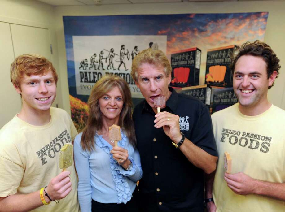 Second from right, Marty Sands, founder and CEO of Paleo Passion Foods, eats one of his company's Paleo Passion Pops at the company's Greenwich office, Wednesday, Oct. 1, 2014. Second from left is Kim Sands, Marty's wife, at left is Jon Andrews, sales and distribution for Paleo Passion, and at right is Ward Waesche, general operations and administration for the company. The Paleo Passion Pop is an ice pop treat containing only natural ingredients, fruit, spices and important superfoods such as chia seeds, ginger and green tea. Photo: Bob Luckey / Greenwich Time