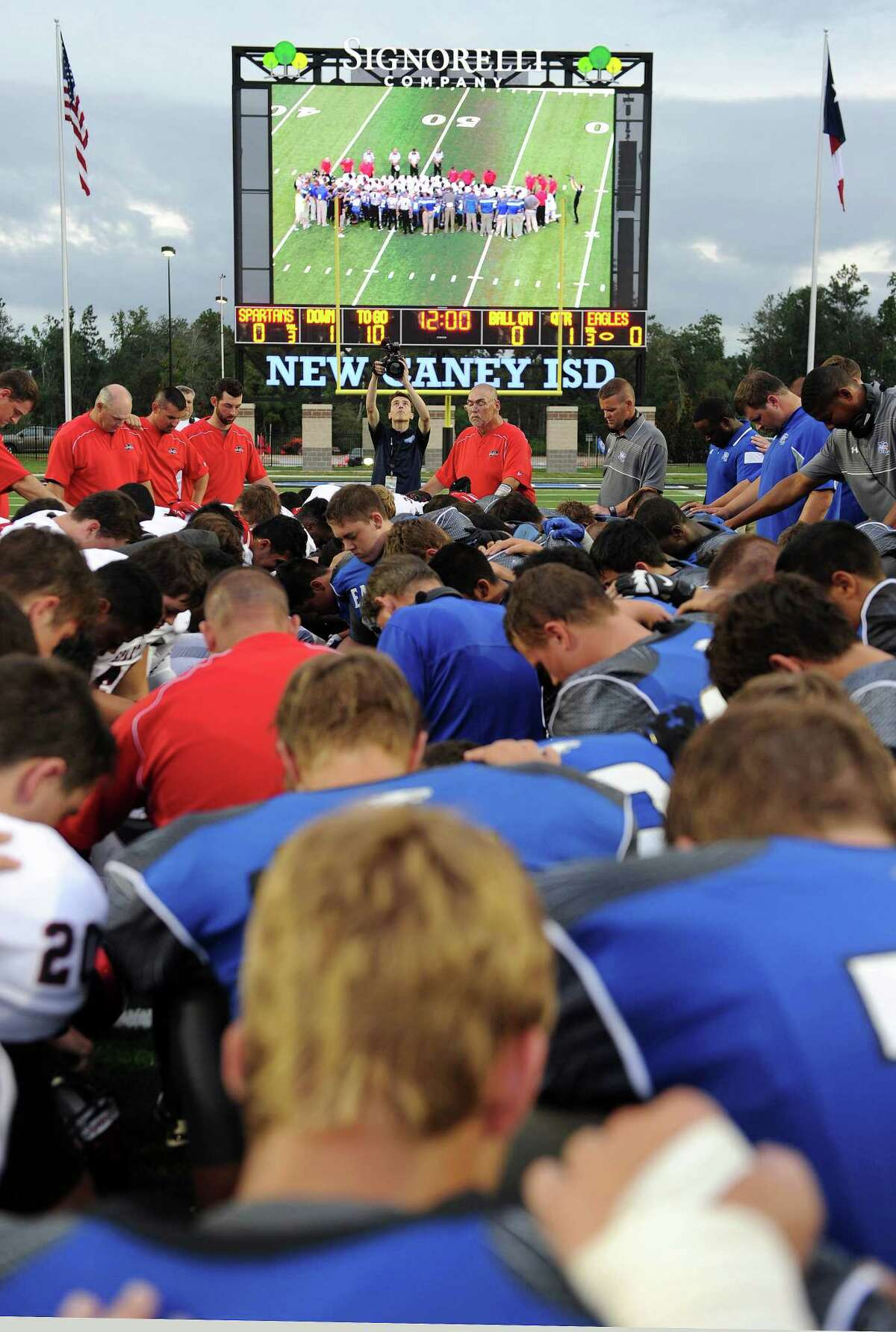 New Caney and Porter football players pray together at the middle of the field that is displayed on the largest video scoreboard for a high school in the United States before a high school football game, Friday, September 12, 2014, at Texan Drive Stadium in Porter, TX. (Photo: Eric Christian Smith/For the Chronicle)