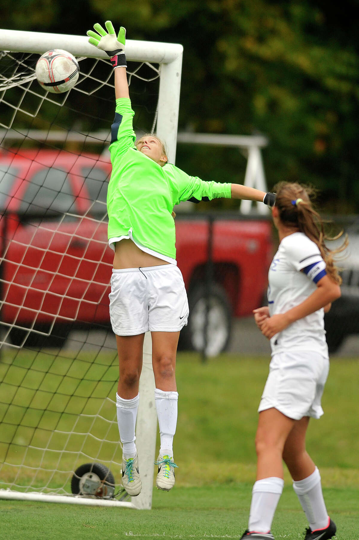 Darien goalie Kate Fiore leaps unsuccessfully for the ball from the free kick off of Westhill's Jessica Laszlo during their soccer game at Darien High School in Darien, Conn., on Wednesday, Oct. 1, 2014. Westhill won, 3-1.