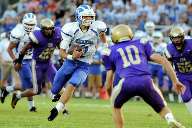 Shaker's quarterback Matt Woods, center, carries the ball during their football game against CBA on Friday, Sept. 5, 2014, at Christian Brothers Academy in Colonie, N.Y. (Cindy Schultz / Times Union) Photo: Cindy Schultz / 00028436A