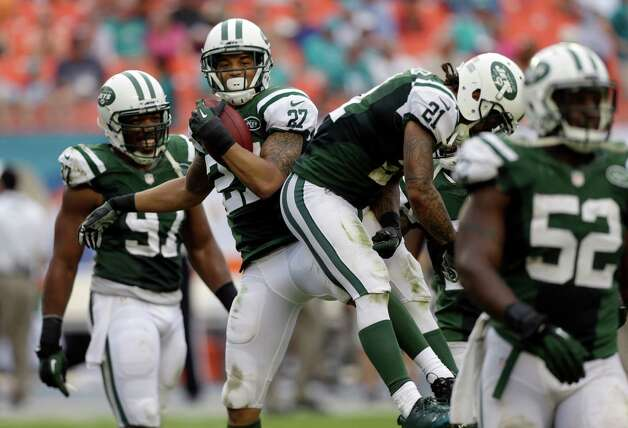 New York Jets cornerback Dee Milliner (27) celebrates with teammates after intercepting a pass by Miami Dolphins quarterback Ryan Tannehill during the fourth quarter of an NFL football game in Miami Gardens, Fla., Sunday, Dec. 29, 2013. The Jets won 20-7. (AP Photo/Alan Diaz) ORG XMIT: SLS115 Photo: Alan Diaz / AP