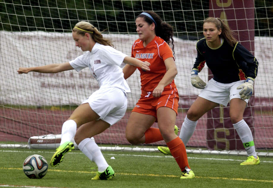 St. Joseph's Lindsey Savko gets this ball past Danbury goalie Allie Smith, at right, to score, during girls soccer action in Trumbull, Conn., on Tuesday Oct. 1, 2014. Photo: Christian Abraham / Connecticut Post