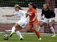 St. Joseph's Lindsey Savko gets this ball past Danbury goalie Allie Smith, at right, to score, during girls soccer action in Trumbull, Conn., on Tuesday Oct. 1, 2014.