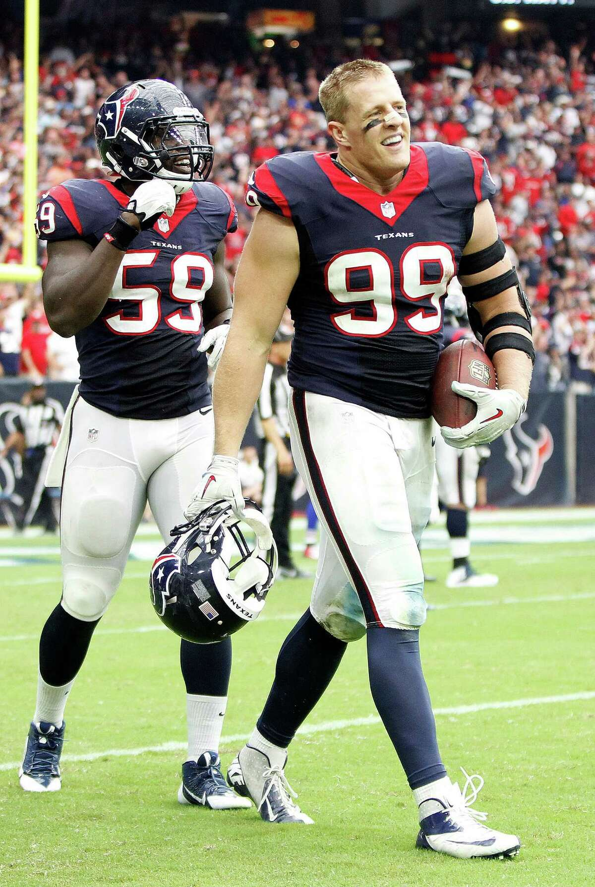 Former Defensive Player of the Year J.J. Watt (99) comes off the field with his interception ball during the third quarter of the Texans victory over the Bills last week. ( Karen Warren / Houston Chronicle )