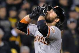 San Francisco Giants' Brandon Crawford points skyward as he heads home after hitting a grand slam during the fourth inning of the NL wild-card playoff baseball game against the Pittsburgh Pirates on Wednesday, Oct. 1, 2014, in Pittsburgh. (AP Photo/Don Wright)