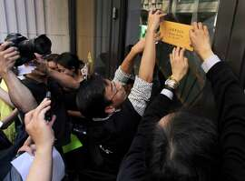Demonstrators supporting the Hong Kong democracy movement tape a letter addressed to Hong Kong Chief Executive Leung Chun-ying at his government's Economic and Trade Office in the Financial District in San Francisco.