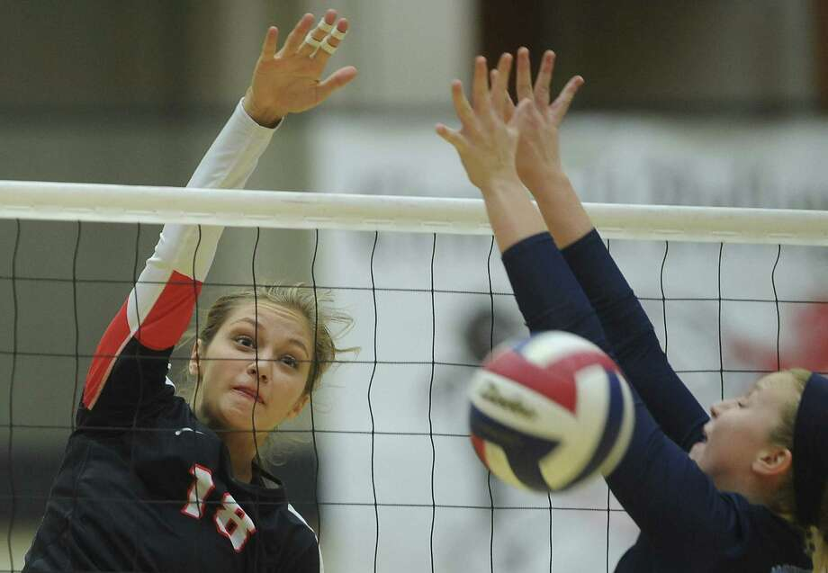 Churchill's Taylor Martinez (left) spikes the ball as Meghan Parker of Johnson defends Wednesday night at Littleton Gym. Photo: Billy Calzada / San Antonio Express-News / San Antonio Express-News