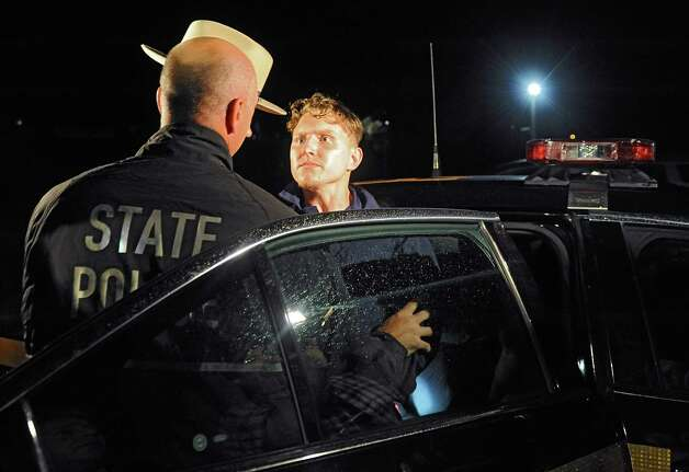 Shane Harding, 25, stares down an officer before putting up a struggle as the police put him in the state police car after his arraignment at North Greenbush Town Court on Wednesday, Oct. 1, 2014 in Wynantskill, N.Y. Harding, a registered sex offender raped a woman in Massachusetts, used a weapon to force her to drive him to North Greenbush and then ordered a man to drive him to Saratoga Springs where he was taken into custody Wednesday after a search that caused Skidmore College to order students to lock their doors. (Lori Van Buren / Times Union) Photo: Lori Van Buren / 00028864A