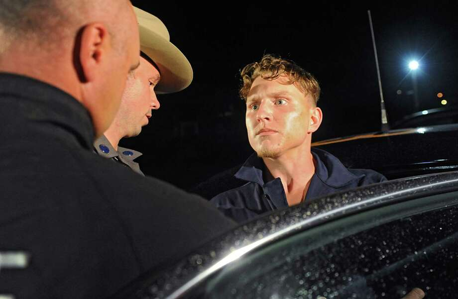 Shane Harding, 25, stares down an officer before putting up a struggle as the police put him in the state police car after his arraignment at North Greenbush Town Court on Wednesday, Oct. 1, 2014 in Wynantskill, N.Y.  (Lori Van Buren / Times Union) Photo: Lori Van Buren / 00028864A