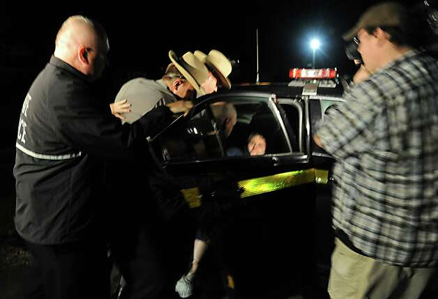Shane Harding, 25, puts up a struggle as the police put him in the state police car after his arraignment at North Greenbush Town Court on Wednesday, Oct. 1, 2014 in Wynantskill, N.Y. (Lori Van Buren / Times Union) Photo: Lori Van Buren / 00028864A