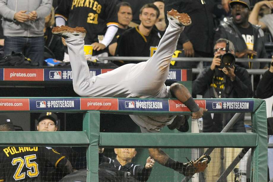 San Francisco Giants third baseman Pablo Sandoval flips over the dugout railing after making a catch on a fly ball by Pittsburgh Pirates' Andrew McCutchen in the seventh inning of the NL wild-card playoff baseball game Wednesday, Oct. 1, 2014, in Pittsburgh. Photo: Don Wright, Associated Press