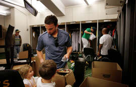 Multitasker Sam Fuld, above, watches over his children Jane, 2, and Charlie, 4, as he empties his locker. Jed Lowrie (below left) and first base coach Tye Waller embrace in the clubhouse.