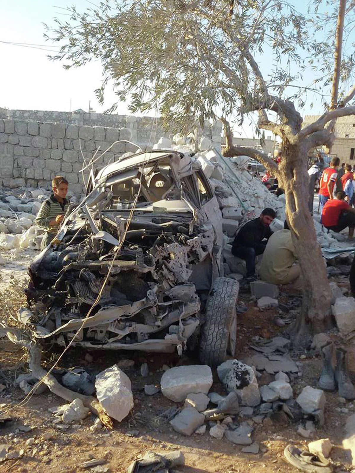 This photo provided by an anti-Bashar Assad activist group Edlib News Network (ENN), which has been authenticated based on its contents and other AP reporting, shows a Syrian boy, left, looking at a destroyed car that activists say was targeted by the coalition airstrikes, in the village of Kfar Derian, a base for the al-Qaida-linked Nusra Front, a rival of the Islamic State group, between the northern province of Aleppo and Idlib, Syria, Tuesday Sept. 23, 2014. Syria said Tuesday that Washington informed President Bashar Assad's government of imminent U.S. airstrikes against the Islamic State group, hours before an American-led military coalition pounded the extremists' strongholds across northern and eastern Syria. (AP Photo/Edlib News Network ENN)