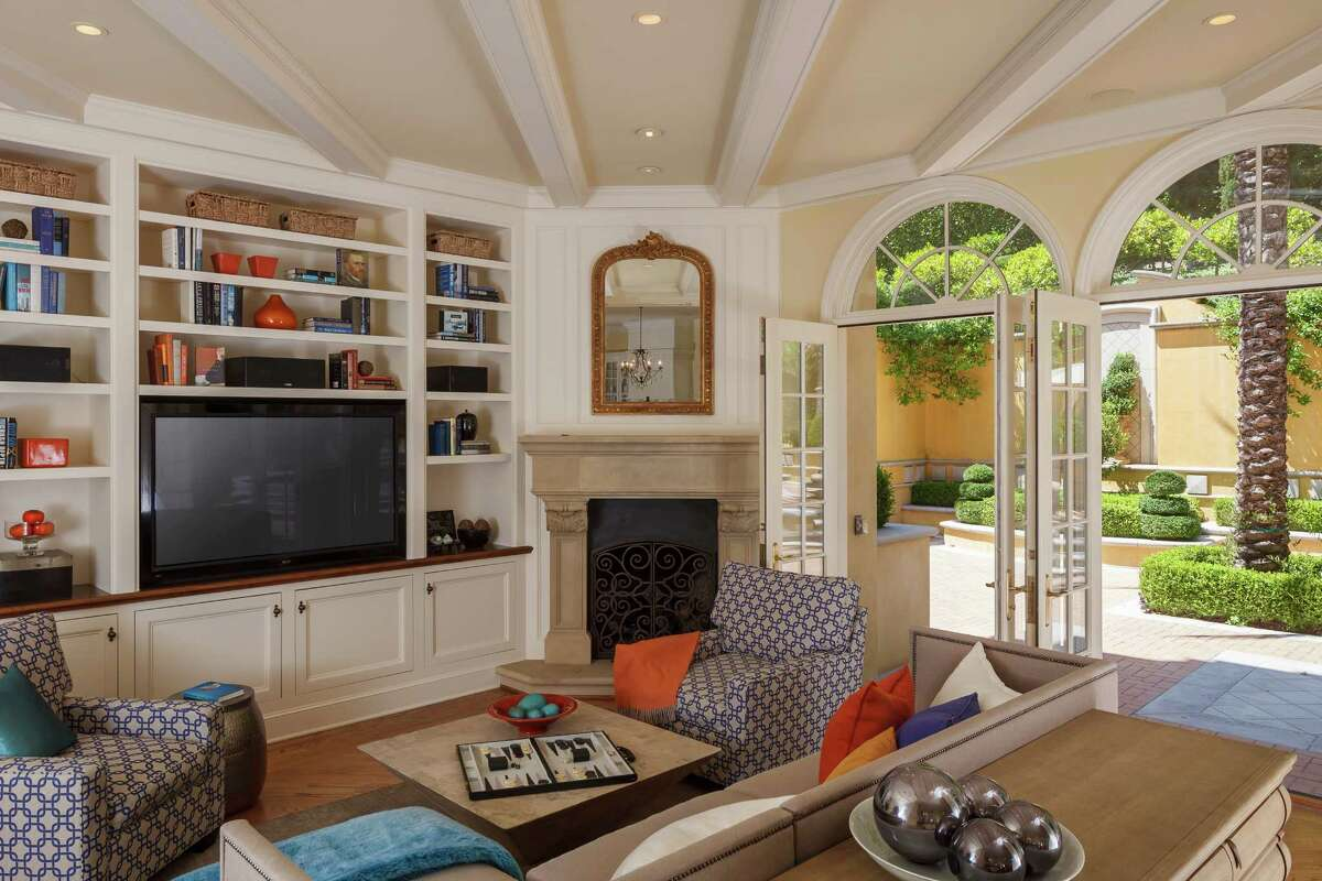Floor-to-ceiling built-in bookshelves, three sets of French doors opening to the backyard and a beamed ceiling highlight the living room.