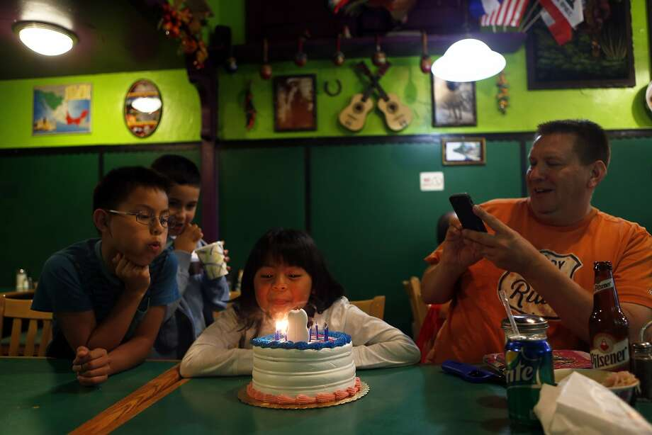 Jim Benny (right) photographs his daughter Terri blows out the candles on her 8th birthday cake as his son, John, 9, (left) and neighbor Gabriel Mendoza, 7, look on at Los Panchos in San Francisco, Calif. on Sunday, September 28, 2014. Photo: Scott Strazzante, The Chronicle