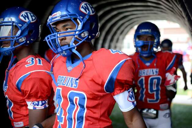 West Brook Bruin Jonathan Thomas, 40, Jacoby Harris, 31, and Nate Parker, 19, charge through the Bruin Tunnel for the match up against the North Shore Mustangs at the Carroll Thomas Stadium September 26, 2014. Photo by Drew Loker.