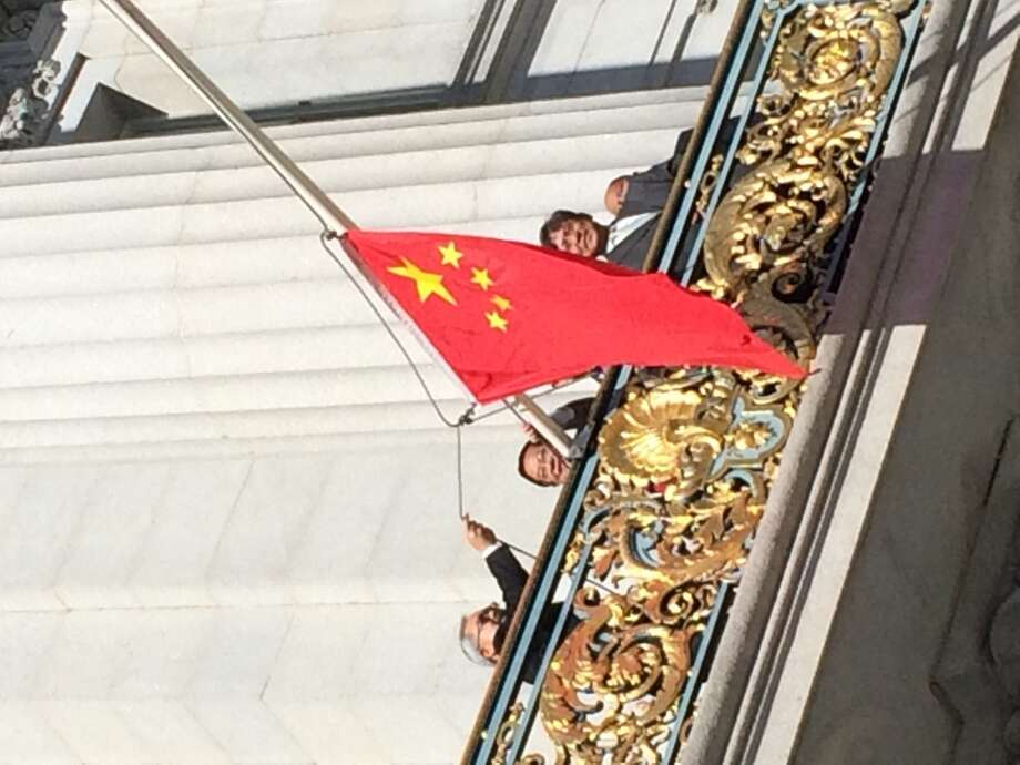 Mayor Ed Lee raises the Chinese flag from his balcony at San Francisco City Hall on Oct. 1, 2014, China's National Day, as a delegation from the Chinese Consulate looks on.  The ceremony came as thousands protested in Hong Kong over China's efforts to curtail democracy there.  (John Cote / The Chronicle)